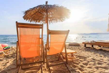 Summer holiday and travel concept. Empty beach chairs with sunshade on sand near the sea with sunlight in background.