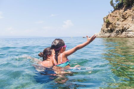 Happy family summer holiday - Mother and daughter enjoy together in the beautiful sea water during vacation