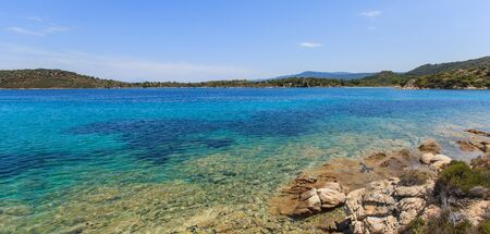 Relaxing sea blue color. Beautiful view on amazing seascape with rock shore with small sand beach. Sithonia. Greece.