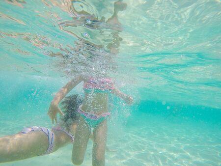 Underwater photo of children swimming in the clear sea water . Summer vacation fun Reklamní fotografie - 148276908
