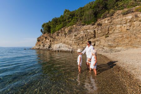 Happy family enjoy at walking on the beach through sea water during summer vacation Reklamní fotografie - 148277113