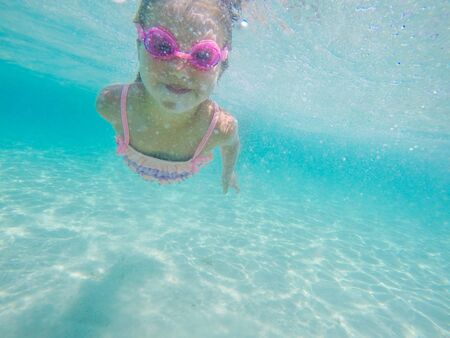 Happy child underwater portrait - Little girl wearing swimming goggles dive and swim in the seawater - Summer vacation fun Reklamní fotografie - 148277044