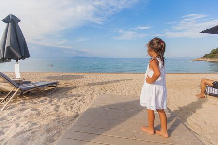 Happy little girl have fun standing on wooden path at sand beach during summer holiday