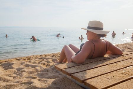 Rear view of woman with hat enjoy summer vacation on sand beach .