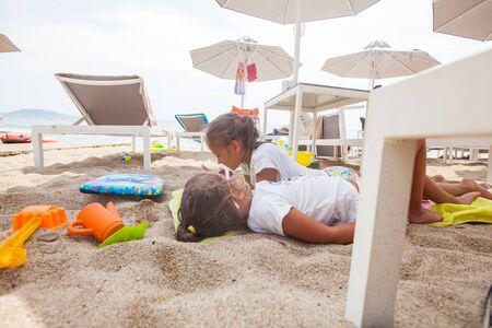 Children relax on sand beach at shade of sun umbrella during summer vacation Reklamní fotografie - 148276909