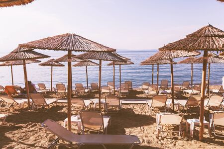 Summer holiday and travel concept - Sunbeds and sunshade on sand beach - Beautiful sea in background - Relaxing lifestyle