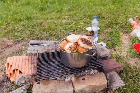 Fireplace for improvised barbecue at campsite in the nature.