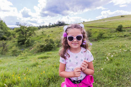 Portrait of happy little girl with flowers, wearing summer sunglasses , nature landscape Stockfoto