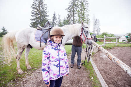 Portrait of smile little girl at ranch, Horseback riding lesson, country landscape Stockfoto
