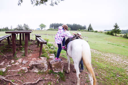 Horseback riding lesson- little girl getting a horse at ranch , country landscape