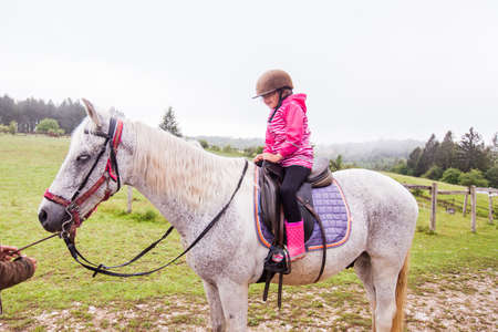 Horseback riding lesson- little girl ride a horse at ranch , country landscape, daylight