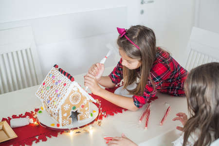 Little girl decorating Christmas gingerbread house at home, Xmas collection