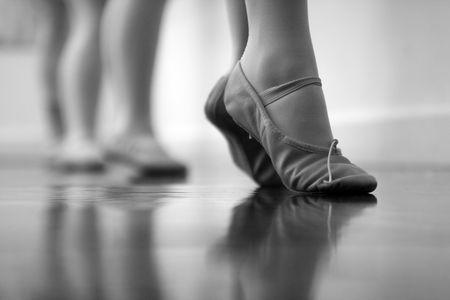 발레 댄서의 발과 다리. 의도적으로 고감도 ISO로 촬영하여 선택적인 소음 제거가 적용된 거친 느낌을줍니다. 검정색과 흰색