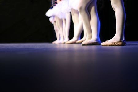 applied: Dancers on stage during a recital. Noise reduction was applied on the floor and the dancers in the background but not the foreground dancers. Stock Photo