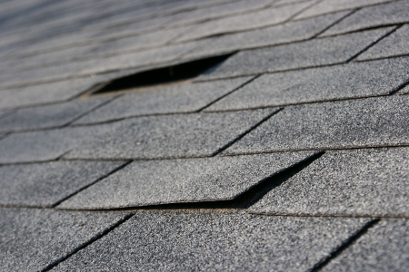 damaged roof: Roofing trouble - damage to shingles that needs repair - home maintenance series. Narrow DOF