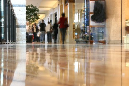 People walking thru the mall - photograph taken from the floor giving a low-angle view and the people shopping are blurred and appear as ghosts