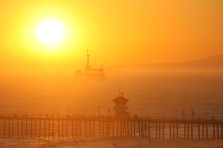 An offshore oil rig lit from behind by the setting sun which is going down in a blaze of glory. photo