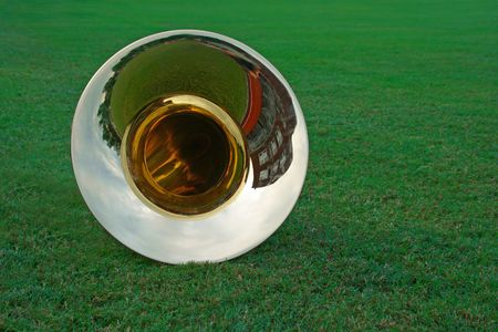 marching: As the marching band practices off to the side, a tuba is resting in the grass of the football field. Stock Photo