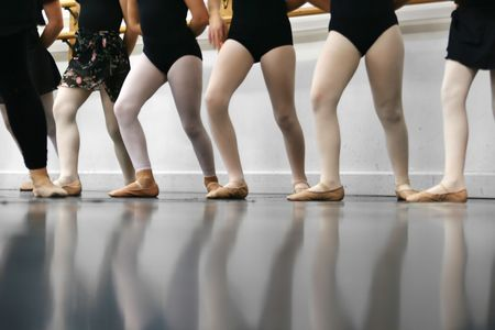 recital: Young dancers are learning - theyre all in a line trying to repeat what the instructor has shown them.