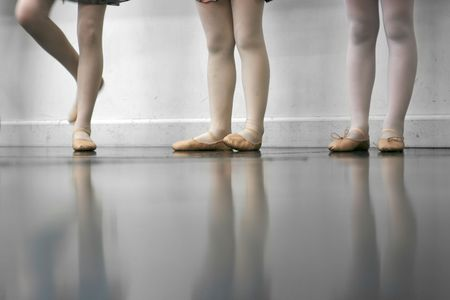 Young dancers are learning - theyre witing to see what the instructor says to do next... low angle shot of just their feet and legs - this view has had the color removed from the floor and wall. Stock Photo