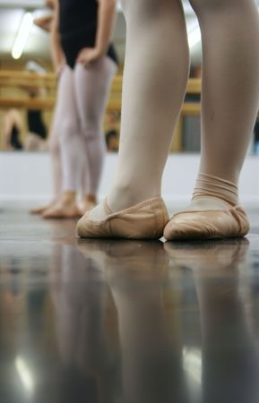 Young dancers are learning - theyre all in a line trying to repeat what the instructor has shown them. photo