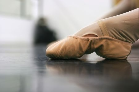 tights: Young dancers are learning - theyre witing to see what the instructor says to do next... low angle shot of just their feet and legs - this view has had the color removed from the floor and wall. Stock Photo
