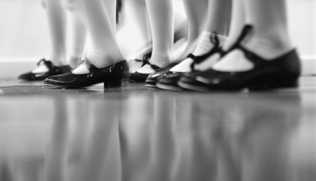 Young dancers are learning - this group is vigorously tapping with tap shoes. Lots of motion - Black and white view