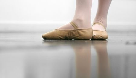 Young dancer... low angle shot of just feet and legs - this view has had the color removed from the floor and wall. photo