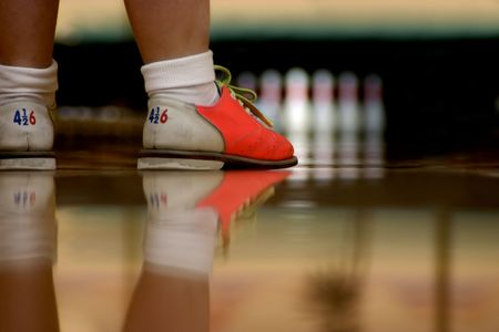 Modern bowling shoes have bright colors. A low angle shot right along the alley showing shoes and their reflection in the highly polished wood. Focus is on bowlers shoes but the pins are visible in the background