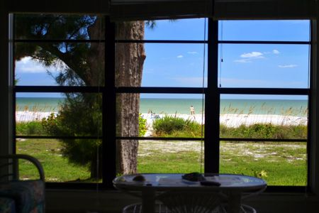 window view: An interesting view of a beach taken from inside the resort. Obviously drawing the viewer outside but nicely framed by the window frames themselves. A bit of interior furniture is also visible. Focus is on the beach.