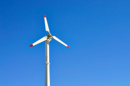 On a bright sunny fall day, a windmill sits waiting for the wind to blow photo