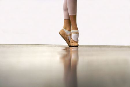 A young ballerina learning how to stand tall on her toes (but not yet on point). Stock Photo