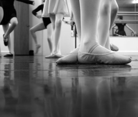 ballet shoes: A ballerina practicing moves in the studio with others... a bit of noise exists in the image - original ISO 1600 but ive cleaned it up a good bit tho some noise is still evident. Black and white