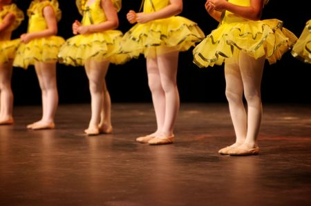 Dancers on stage during a recital in bright costumes. Noise reduction was applied on the floor and the dancers in the background but not the foreground dancers. Stok Fotoğraf