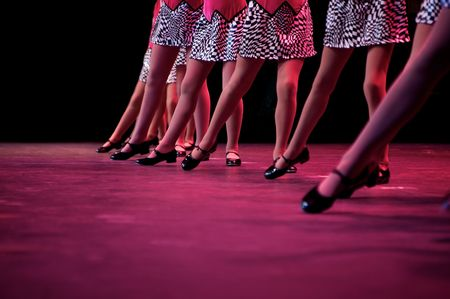 Dancers on stage during a recital in bright costumes. Noise reduction was applied on the floor and the dancers in the background but not the foreground dancers. Stock Photo