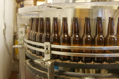 A root beer factory bottle filling line getting ready to fill bottles.