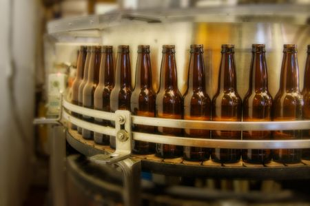 brewery: factory bottle filling line getting ready to fill bottles.