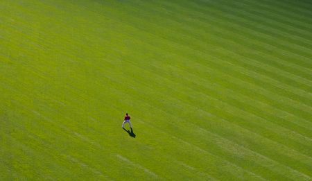outfield: A baseball player stands alone out in the outfield
