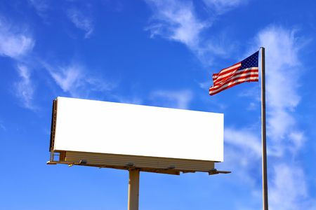 A roadside billboard with an American Flag next to it. The sky has been carefully replaced with another similarly lit sky but with more clouds photo