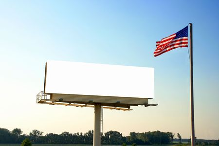 A roadside billboard with an American Flag next to it. This view is a bit further out showing trees in the background. The railings were also removed in this version. photo