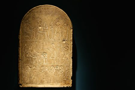 A stone tablet with heiroglyphics telling a story.