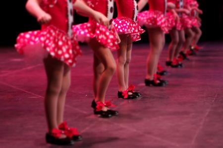 show off: Performing on stage, a group of young dancers show off their talent and bright costumes - image highlights a narrow depth of field on the girl in the middle of the line