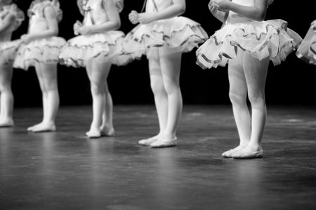 Dancers on stage during a recital in bright costumes but the image is B&W Stock Photo