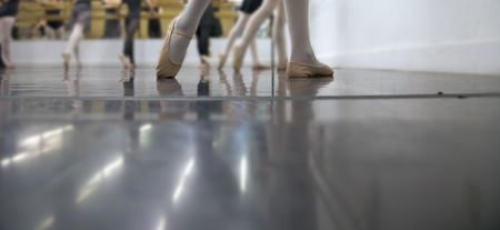Young dancers are learning - theyre witing to see what the instructor says to do next... low angle shot of just their feet and legs photo
