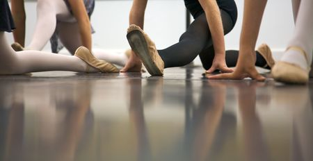 Young dancers are learning - theyre witing to see what the instructor says to do next... low angle shot of just their feet and legs