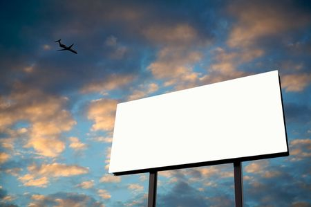 Brand new billboard in the setting sun with a jet flying over photo