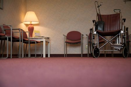 A doctors office waiting room with a wheelchair - focus is on the wheelchair photo