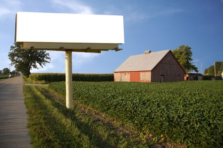 Brand new billboard in the field next to a farm - great farming advertisement! Stock Photo