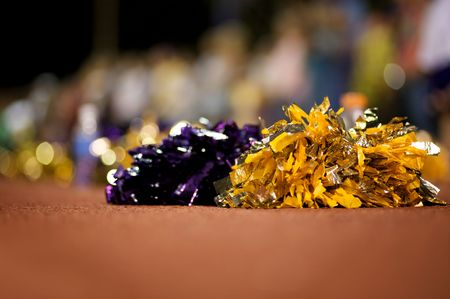 A close up of cheerleader poms on the ground with the crowd in the background out of focus - narrow DOF