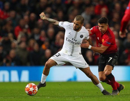 MANCHESTER, ENGLAND - FEBRUARY 12 2019: Dani Alves of PSG  and Alexis Sanchez of Manchester United during the Champions League match between Manchester United and Paris Saint-Germain at Old Trafford S